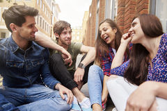 Two couples sitting on pavement Royalty Free Stock Photos