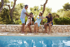 Two couples socialising by a pool outdoors make a toast Stock Image
