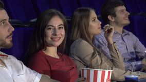 Two couples spend a double date at the cinema and watch the movie. Four people are sitting in the cinema. They are in pairs, they have a double date. Couples eat stock photography