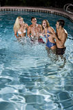 Two couples in swimming pool at night Royalty Free Stock Photo