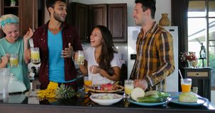 Two Couples Talking In Kitchen Tasting Fresh Juice, Young Man And Woman Drinking Together Happy Smiling. Slow Motion 60 stock footage