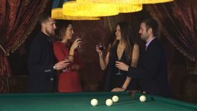 Two couples talking near the pool table and drink. Two couples celebrate the holiday stock footage