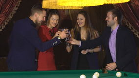 Two couples talking near the pool table and drink. Two couples celebrate the holiday, slow motion stock video footage