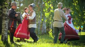 Two couples in traditional Russian clothes dancing on the field by the accordion music. Mid shot stock footage