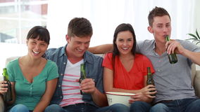 Two couples watching the television together. In a bright living room stock footage