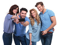Two couples of young people taking their picture with phone Royalty Free Stock Image