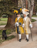 Two Courtiers. Annecy,France-March 15,2014:Two men disguised in medieval courtier's costumes with a black dog walking in a park during the Annecy Venetian Royalty Free Stock Photos