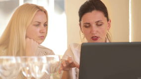 Two coworkers business women discussing their restaurant ideas using laptop. 
