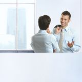 Two coworkers chatting in office Stock Images