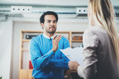Two coworkers discussing business project in modern office.Successful confident hispanic businessman talking with woman Stock Image
