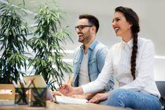 Two coworkers discussing business strategy in modern office. Two young coworkers discussing business strategy in modern office Stock Photography