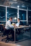 Two gentlemen staying up late in office working. Two coworkers finishing up on some work in late hour. Businessmen sitting at desk facing each other working on royalty free stock photography