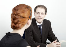 Two coworkers having a discussion. Two business colleagues, a men and woman, having a discussion with the men speaking whlile facing the camera Royalty Free Stock Image