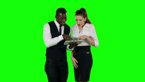 Two coworkers look at a laptop together. Green screen. Businessmen looking at their laptop, young business people cooperate and shake hands, serious working stock video