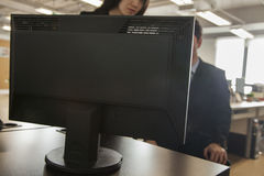 Two coworkers looking at computer monitor Stock Photos