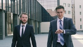 Two coworkers walking towards the office center to hold a meeting stock video footage