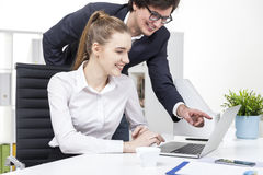 Two coworkers watching a funny video at lunch break Royalty Free Stock Photo