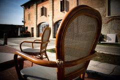 Two cozy chairs standing in the yard near the old building stock image