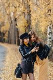 two cozy young girls walk at autumn park road an make photos stock images