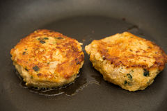 Two Crab Cakes Browning in Hot Oil Royalty Free Stock Photos