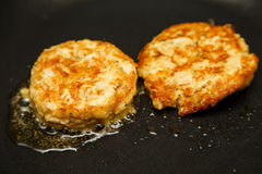 Two Crab Cakes Browning in Pan Stock Images