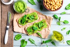 Two crackers with green spinach humus royalty free stock photos