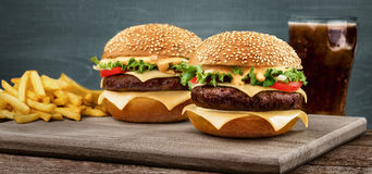 Two craft beef burgers on wooden table on blue background. Royalty Free Stock Photography