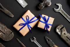 Two craft gifts with vintage old tools on black paper background. Fathers day concept. Flat lay.  stock photo