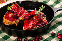 Two cranberry glazed chicken breasts in skillet Stock Photo