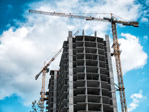 Two Crane near construction building. Two Crane near construction building on blue sky background Stock Image