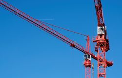 Two cranes. Two red cranes against a blue sky royalty free stock photo