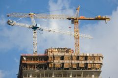 Two cranes. On top of new building under construction royalty free stock photography