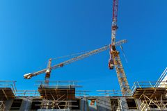 Two cranes against the blue sky. Two cranes on the construction of a residential modern apartment building. renovation of the city quarter stock photo