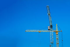 Two cranes against the blue sky. Stock Photos