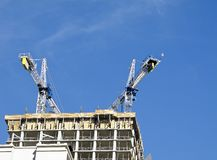 Two cranes atop new construction Royalty Free Stock Photo