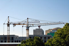 Two cranes and buildings under construction Stock Photos