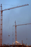 Two cranes on a construction site, a fittings in an unfinished house, a foggy evening twilight Stock Photography