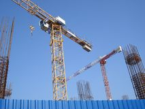 Two cranes on construction site. Two cranes and reinforcing bars on construction site, beyond metallic blue fence stock photography