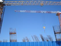 Two cranes on construction site. Two cranes and reinforcing bars on construction site, beyond metallic blue fence royalty free stock images