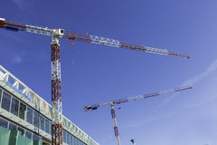 Two cranes in construction site Stock Images