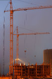 Two cranes on the construction site, unfinished house, foggy evening, building lighting on twilight Stock Image