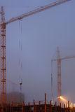 Two cranes on the construction site, unfinished house, foggy evening twilight, building lighting Royalty Free Stock Image