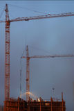 Two cranes on the construction site, unfinished house, foggy evening twilight, building lighting Stock Photos