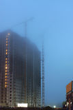 Two cranes on the construction site, unfinished houses, fog covers the upper floors, evening twilight, the lighting of Stock Photo