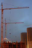 Two cranes on the construction site, unfinished multi-storey house, foggy evening twilight, building lighting Royalty Free Stock Photo
