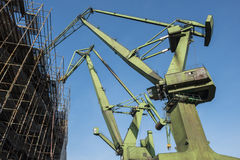 Two cranes in front of the scaffold. View of the shipyard cranes and scaffolding Royalty Free Stock Image