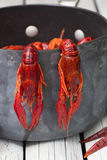 Two crayfish hanging on the tails. Boiled crawfish. Woden background. Rustic style. Stock Photo