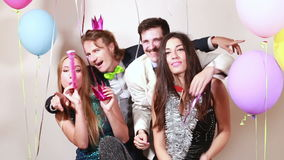 Two crazy couples having a great time in photo booth. Two crazy couples having great time in party photo booth stock footage