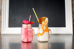 Two crazy milkshakes, with a blank blackboard Royalty Free Stock Images