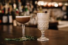Two creamy alcoholic cocktails with a bar in the background. Two creamy alcoholic cocktails garnished with rosemary and cinnamon with a bar in the background royalty free stock photography